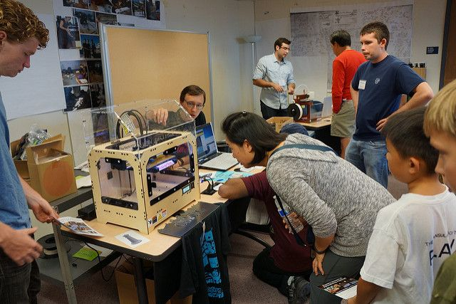 personas mirando impresora 3D
