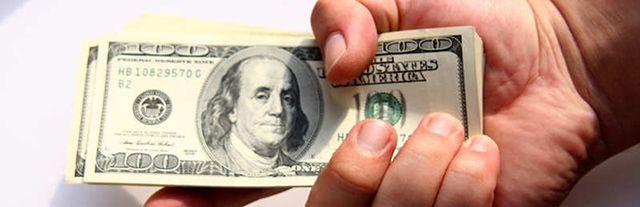 Manojo de dólares en una mano