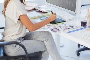 Un editor de fotos se sienta en su escritorio y utiliza un lápiz para retocar las fotos en su ordenador