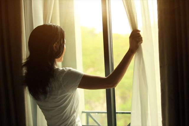 Mujer de apertura de las cortinas