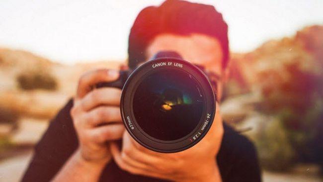 Fotógrafo que toma tiro de la lente Canon EF