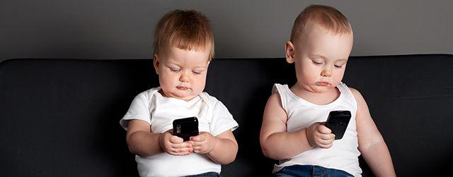 niño y niña jugando con los teléfonos móviles