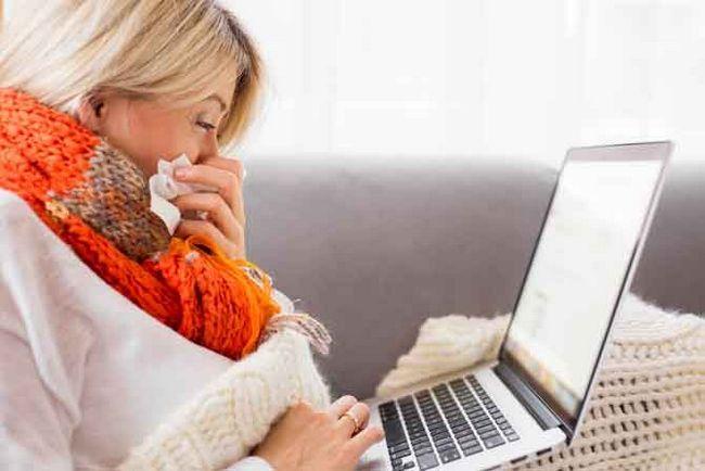 mujer enferma que trabaja en la computadora portátil