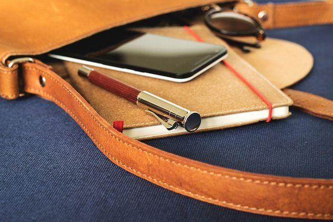 Cuaderno y el teléfono colgando hacia fuera de una bolsa