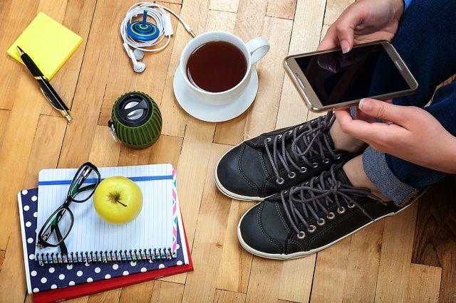 Persona con teléfono inteligente, una taza de café, bloc de notas, etc.
